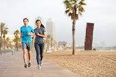 Running couple jogging on Barcelona Beach, Barceloneta. Healthy lifestyle people runners training outside on boardwalk. Multiracial couple, Asian woman, Caucasian fitness man working out, Spain. poster