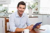 Portrait of a smiling young man using digital tablet at home poster