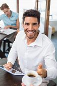 Smiling young man receiving coffee while using digital tablet in the coffee shop poster