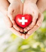 family health, charity and medicine concept - male and female hands holding red heart with cross sign poster