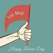Human hand holding a flag with text 1st May on green background, concept for Happy Labour Day.  poster