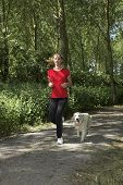 Pretty blond woman running in the woods with her dog poster