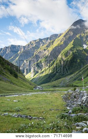 LES CHAPIEUX, FRANCE - AUGUST 27: Mountains chain with lonely chalet at the hill side. The region is a stage at the Mont Blanc tour, which crosses three countries. August 27, 2014 in Les Chapieux.