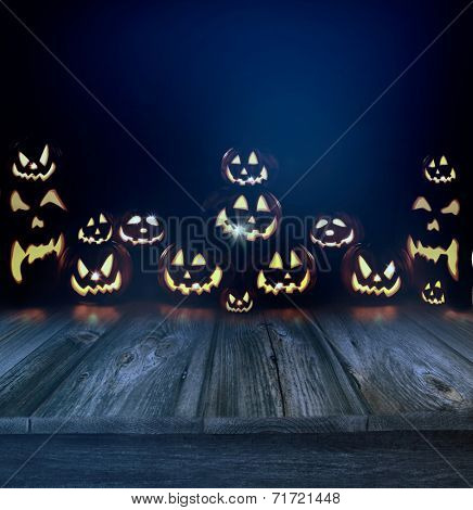 Halloween pumpkins in a dark eerie background and wood floor