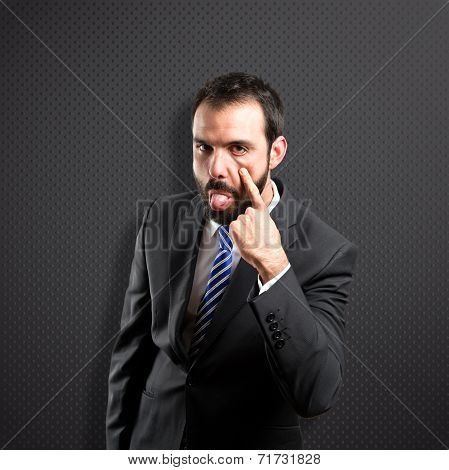 Young Businessman Making A Mockery Over Black Background
