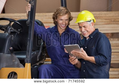Male carpenters using digital tablet together in workshop