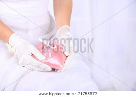 Bride in white dress and gloves holding decorative pillow with wedding rings, close-up, on light background
