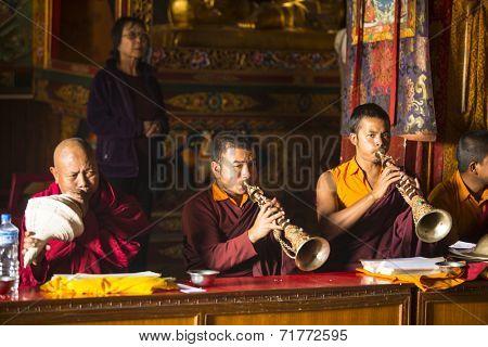 KATHMANDU, NEPAL - DEC 11, 2013: Unidentified Buddhist lama play music near stupa Boudhanath. Stupa is one of the largest in the world, of 1979 is a UNESCO World Heritage Site.