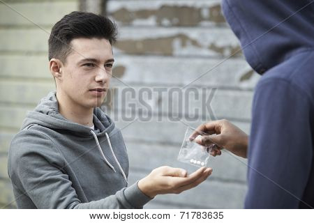 Teenage Boy Buying Drugs On The Street From Dealer