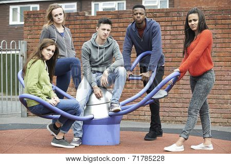 Gang Of Teenagers Hanging Out In Children's Playground