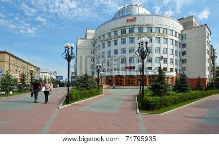 NOVOSIBIRSK, RUSSIA - AUGUST 25, 2014: People walking in front of the headquarter of the West-Siberian Railway. Created in the late XIX century, today the Railway has 9019,8 km of the main railways