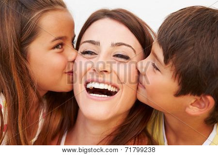 Portrait Of Hispanic Children Kissing Mother