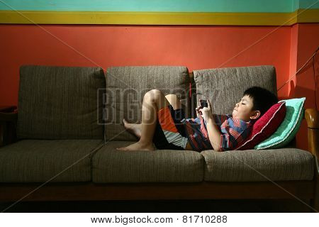 Young kid using a tablet or smartphone on a couch