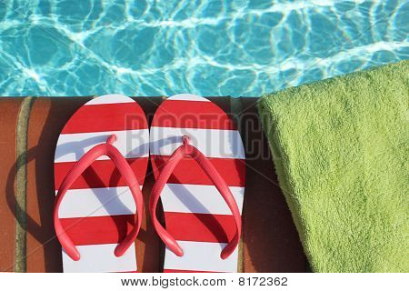 Flip flops by edge of swimming pool