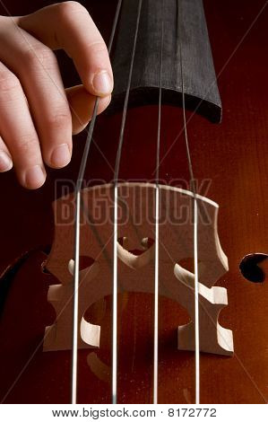Close Up Of A Childhand Is Playing The Cello