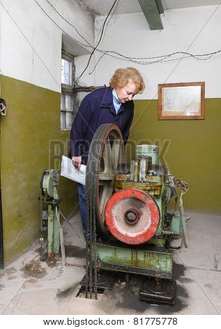Operator woman-engineer in machine room (elevator) check the mechanical equipment. poster