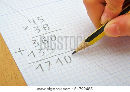 Hand of a child making a multiplication with a pencil. Math. School concept.