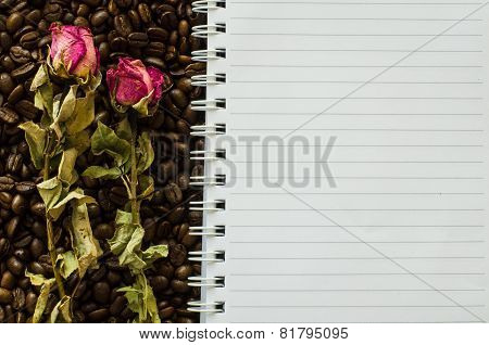 Notebook And Wizened Rose On Coffee Bean Background
