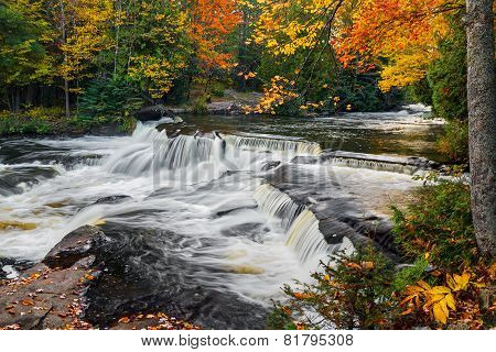 Whitewater cascades over rock ledges with intensely colorful fall foliage all around at Bond Falls in Michigan's Upper Peninsula. poster