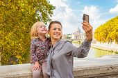 Happy mother and baby girl making selfie on bridge ponte umberto I with view on basilica di san pietro poster