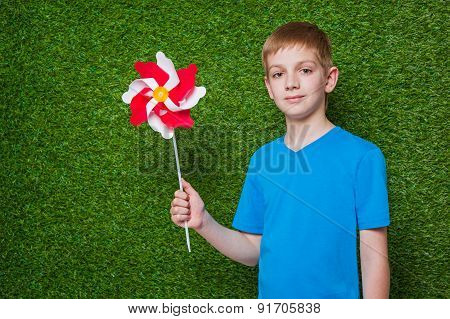 Boy holding pinwheel over grass