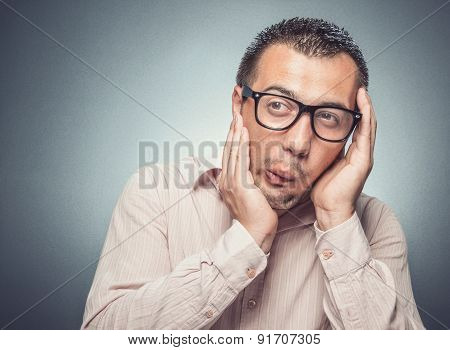 Man in fear touching his face with hands. Close up of a funny afraid businessman over gray background poster