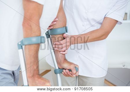 Doctor helping her patient walking with crutch in medical office