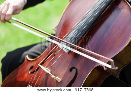 Man's Hands Playing Violoncello Outdoors
