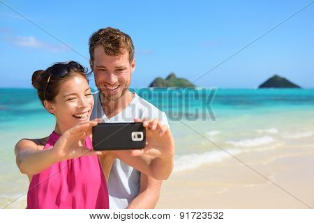Beach vacation couple taking selfie photograph using smartphone, Lanikai beach, Oahu, Hawaii, USA with Mokulua Islands. Couple holding smart phone camera. Young beautiful multicultural Asian Caucasian