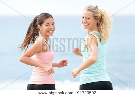 Women running exercising. Two young fit female friends runners smiling jogging on summer beach enjoying healthy lifestyle. Beautiful fitness models turning towards camera in summer.