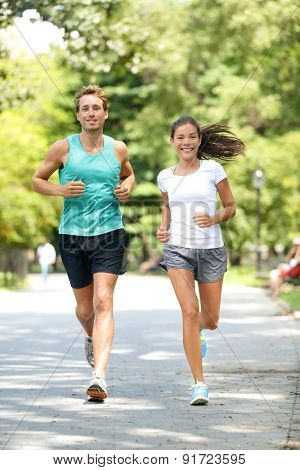 Fitness healthy lifestyle young couple training for marathon outside in Central Park, Manhattan, New York. Asian female model and Caucasian handsome sport fitness male. Happily enjoying jogging.
