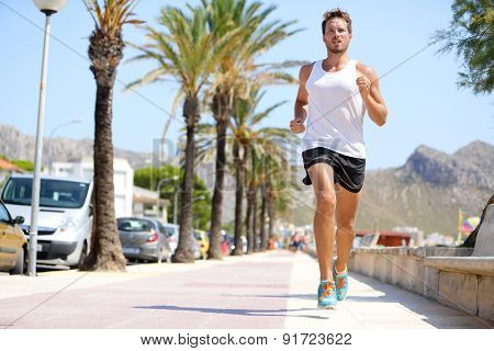 Fit male runner running outside on boardwalk. Young man model training fitness jogging on Mallorca beach city outdoors in summer sun. Palms in background. Healthy lifestyle.