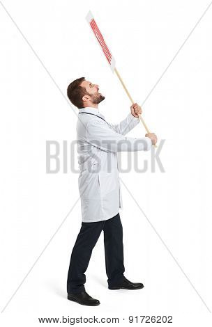 sideview of angry screaming doctor in white cloak holding placard with stop sign and looking up. isolated on white background