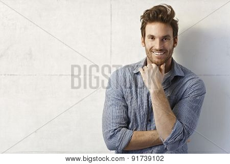 Portrait of handsome young casual man smiling over wall.