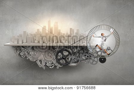 Young businesswoman running in wheel of gears mechanism