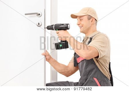 Young male locksmith screwing a screw on a lock of a door with a hand drill isolated on white background