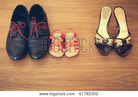 Three pairs of shoes: men, women and children. Baby sandals stand next to men's shoes.