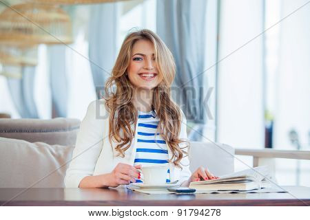 beautiful young girl in outdoor cafe reading a book and drinking coffee. phone. student. business wo