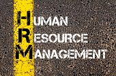 Concept image of Business Acronym HRM as HUMAN RESOURCE MANAGEMENT written over road marking yellow paint line. poster