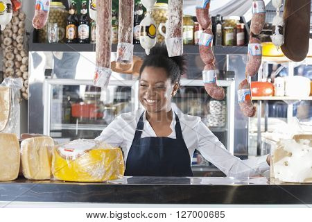Happy Saleswoman In Cheese Shop