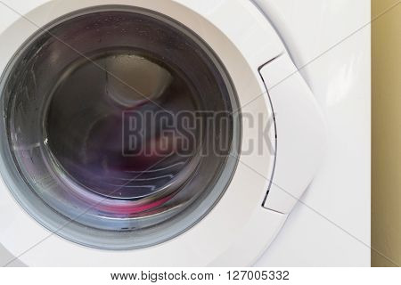 white washing machine with the front loading