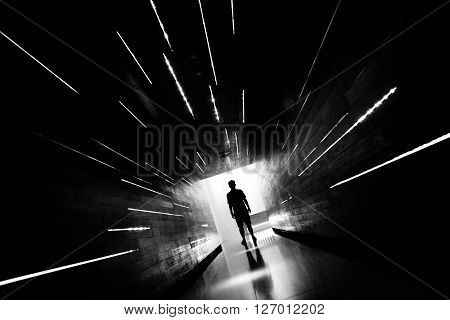 BW shot of Silhouette human standing in a center of corridor. ** Note: Visible grain at 100%, best at smaller sizes