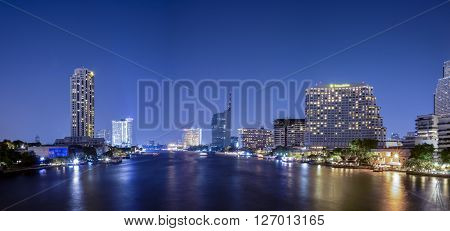 Night light view with modern building and Chao Phraya River in Bangkok Thailand with blue color tone (Panorama landscape at Tak Sin Bridge)