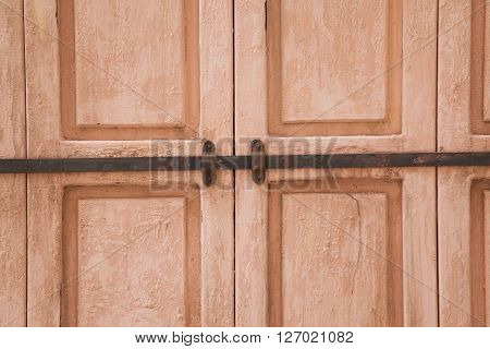 Rose weahtered wood door closed by a rusty rod