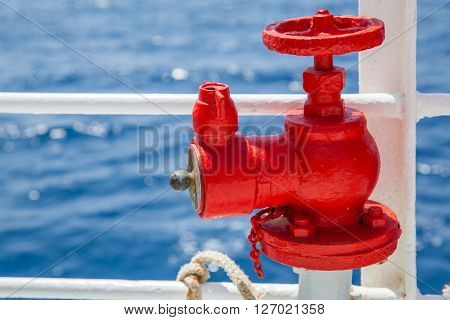 Red fire extinguisher with pipe connector on a boat