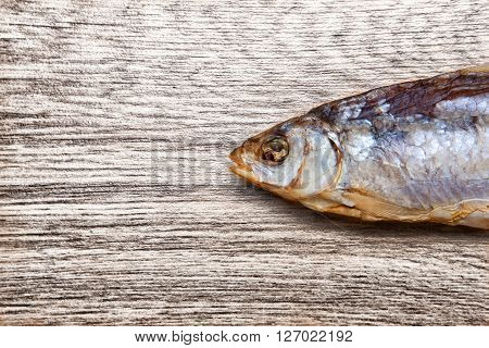 Dry fish close up on a wooden background