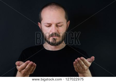 Portrait of an adult man with beard and mustaches on black background, eyes closed, praying and contemplating