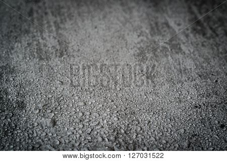 Wet gray concrete background with selective focus.