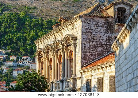 Elaborately ornamented windows with angular pediments on columns and balustrades on an abandoned building in the old city of Dubrovnik