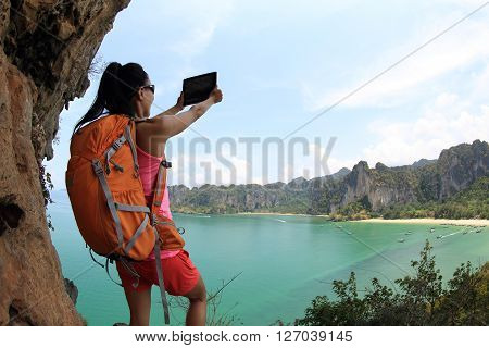 young asian woman hiker taking photo with digital tablet at mountain peak